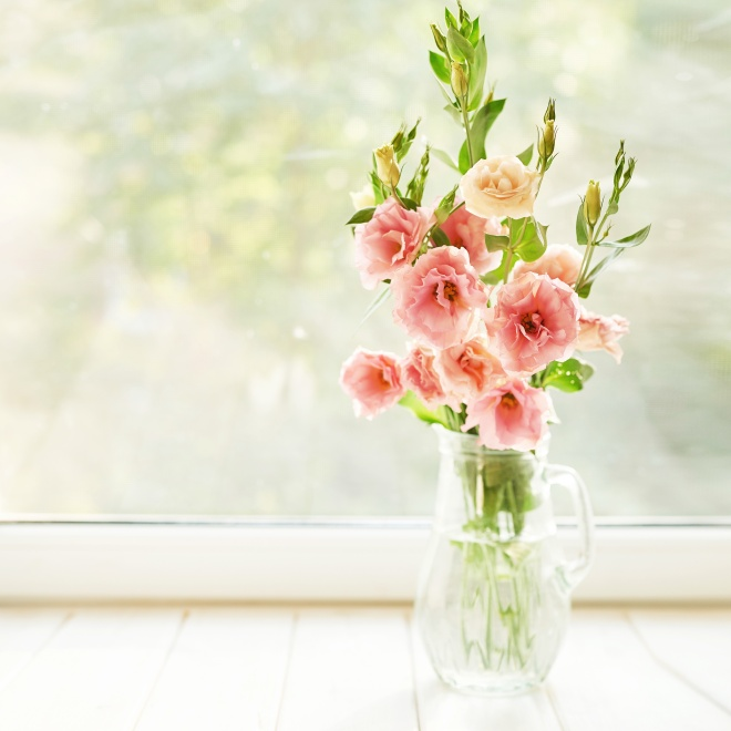 vase with eustoma flowers on a table against the background of a window